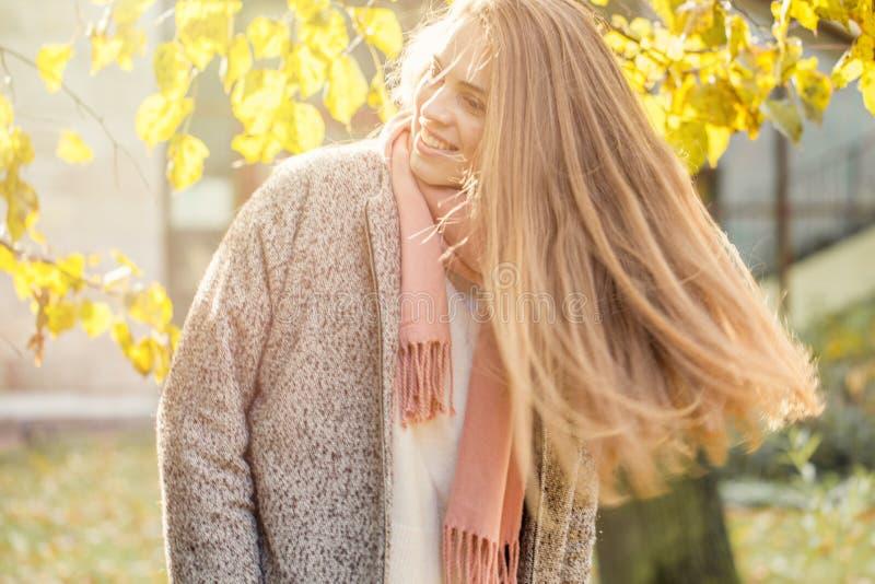 拿着黄色枫叶的美丽的秋天妇女户外 有长发的浪漫女孩在秋天公园 库存照片