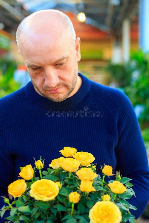 拿着黄色玫瑰的花束一个人, 免版税库存图片
