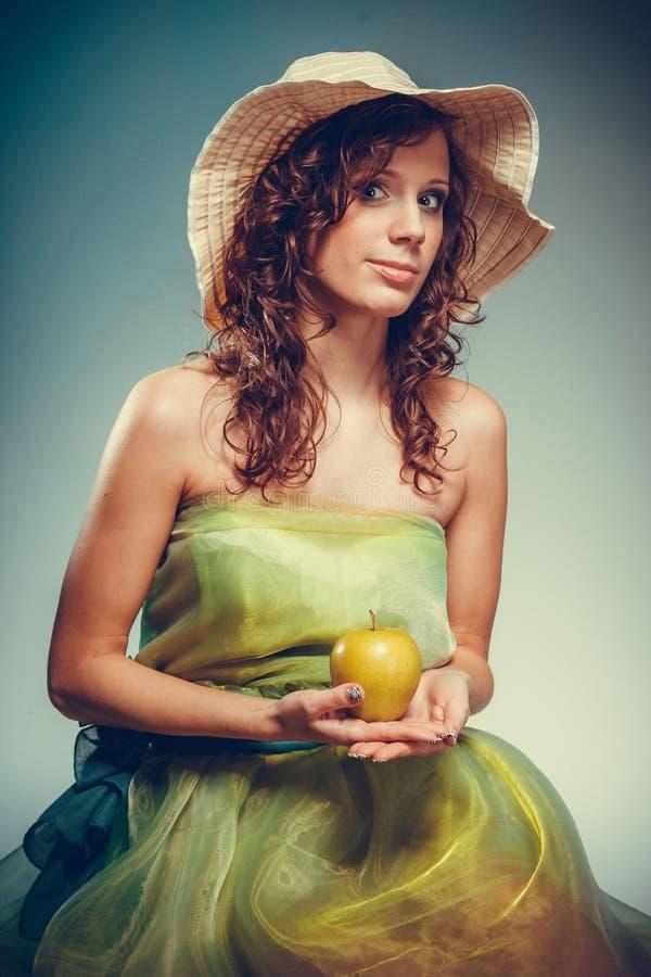 拿着黄色苹果的礼服和帽子的妇女 免版税库存照片