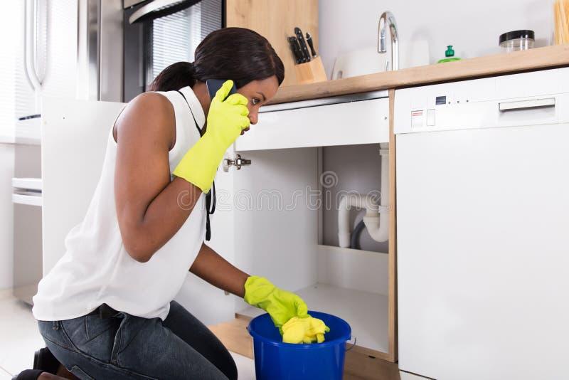 拿着黄色餐巾的妇女告诉水管工 免版税图库摄影