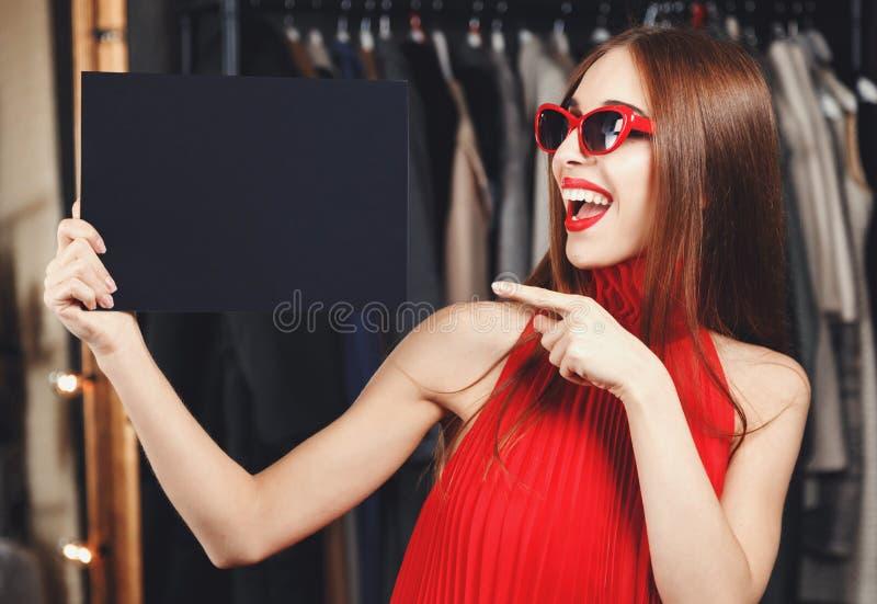 拿着黑卡片的端庄的妇女 免版税图库摄影