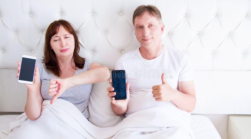 拿着黑屏手机和说谎在床上的中间年迈的夫妇在酒店房间卧室 库存照片