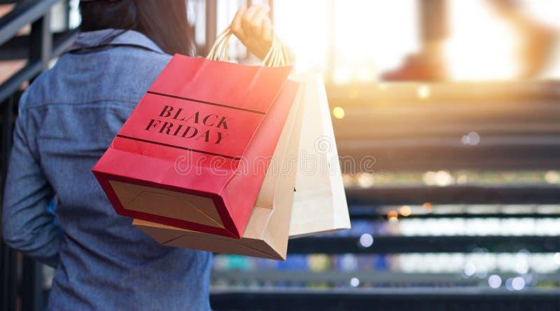 拿着黑星期五购物袋的妇女背面图 免版税库存图片