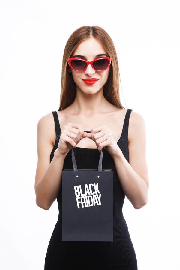 拿着黑星期五购物袋的富有的妇女 库存图片
