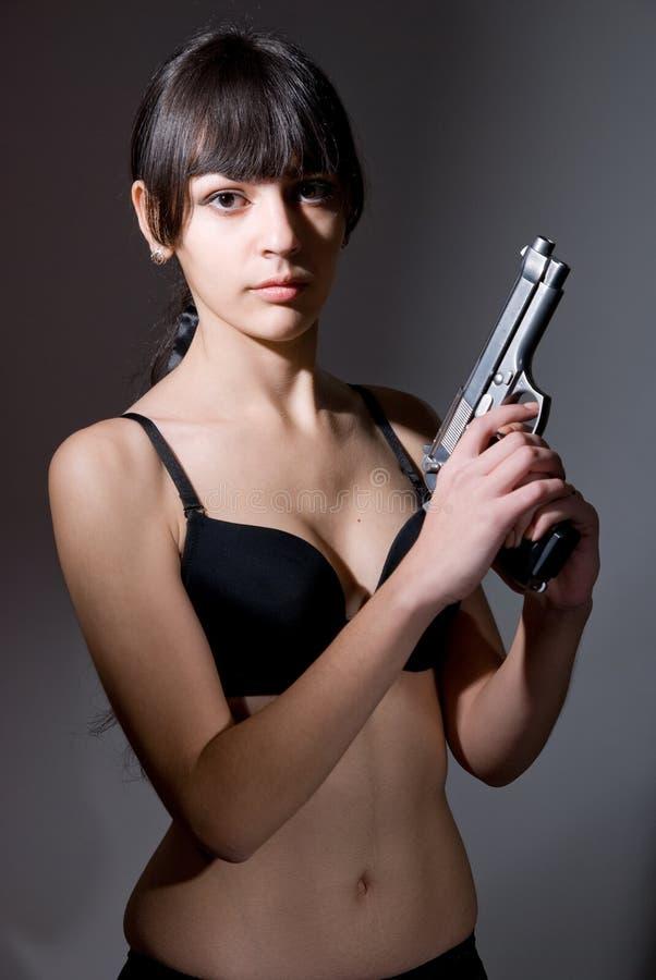 拿着黑色枪的性感的女孩。 免版税库存图片