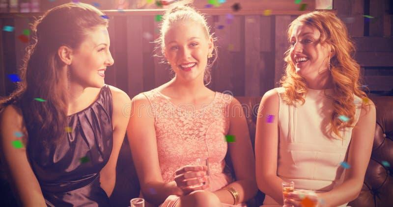 拿着龙舌兰酒的小玻璃在酒吧的三个女性朋友的综合图象 免版税库存图片