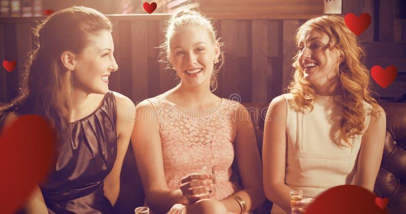 拿着龙舌兰酒的小玻璃在酒吧的三个女性朋友的综合图象 库存照片