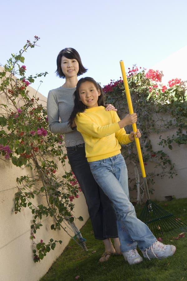 拿着从事园艺的叉子的母亲和女儿 图库摄影