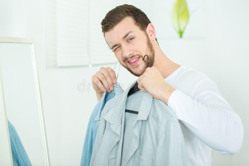 拿着2件衬衣的微笑的愉快的年轻人 库存照片