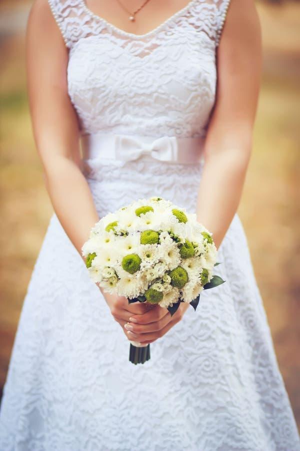 拿着延命菊的花束新娘在她的手上在一婚礼之日有模糊的背景 图库摄影