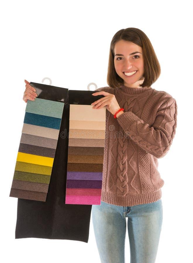 拿着织品样片的毛线衣的美丽的妇女 库存照片