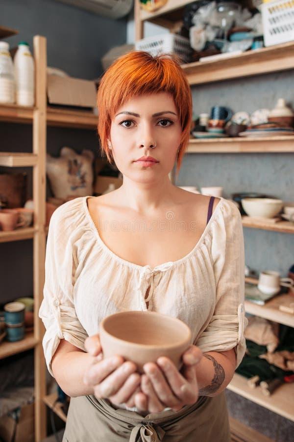 拿着黏土碗的女性陶瓷工在演播室 免版税库存图片