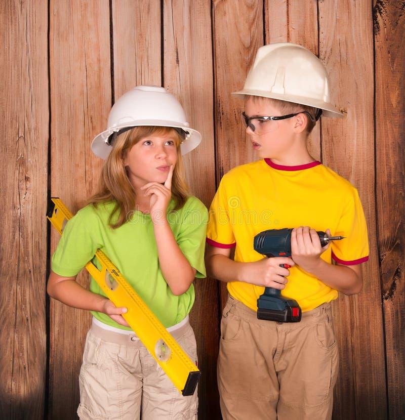 拿着钻子和水平的盔甲的建筑孩子 剪切 库存图片