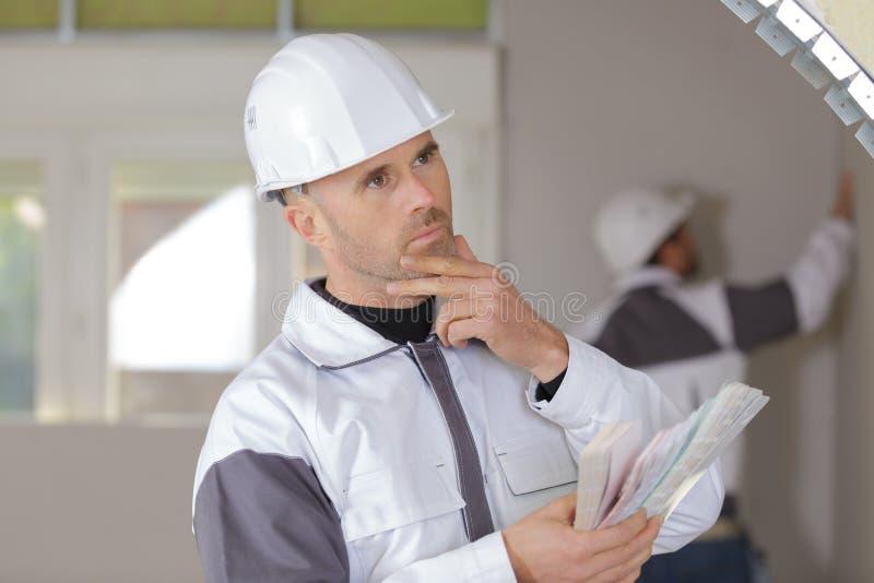 拿着水平仪的迷茫的建筑工人在新房里 免版税库存照片