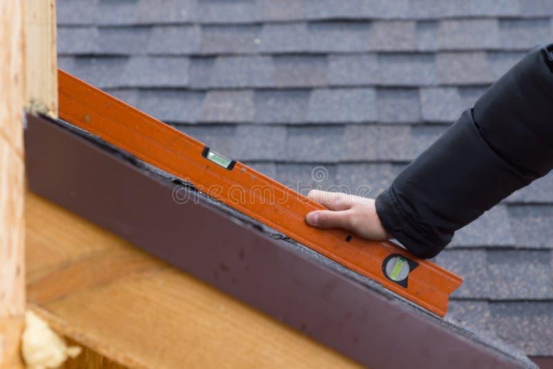 拿着水平仪的建造者或盖屋顶的人 免版税库存图片