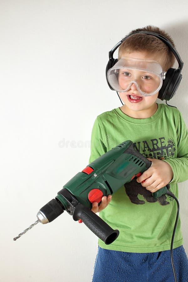 拿着钻床的男孩准备好操练 免版税库存图片