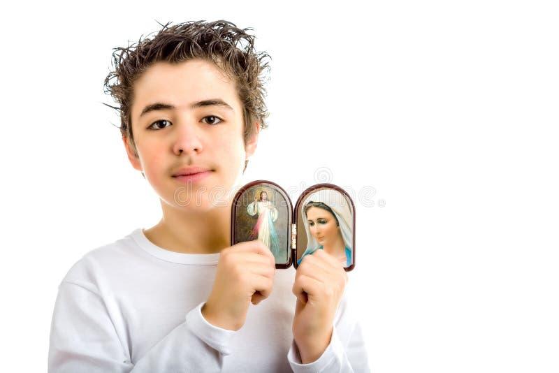 拿着仁慈的耶稣和我们的Medjugorje象的夫人的男孩 库存图片