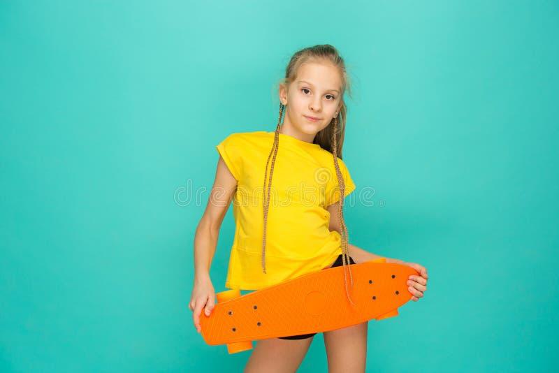 拿着滑板的俏丽的溜冰者女孩 免版税图库摄影