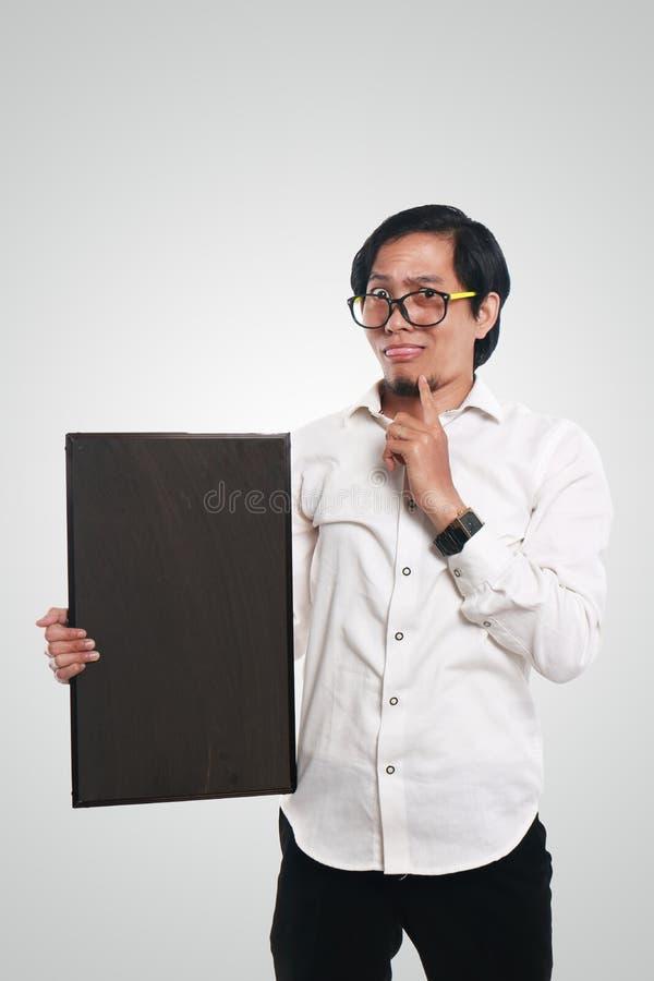 拿着黑板的疯狂的亚洲商人 免版税库存照片