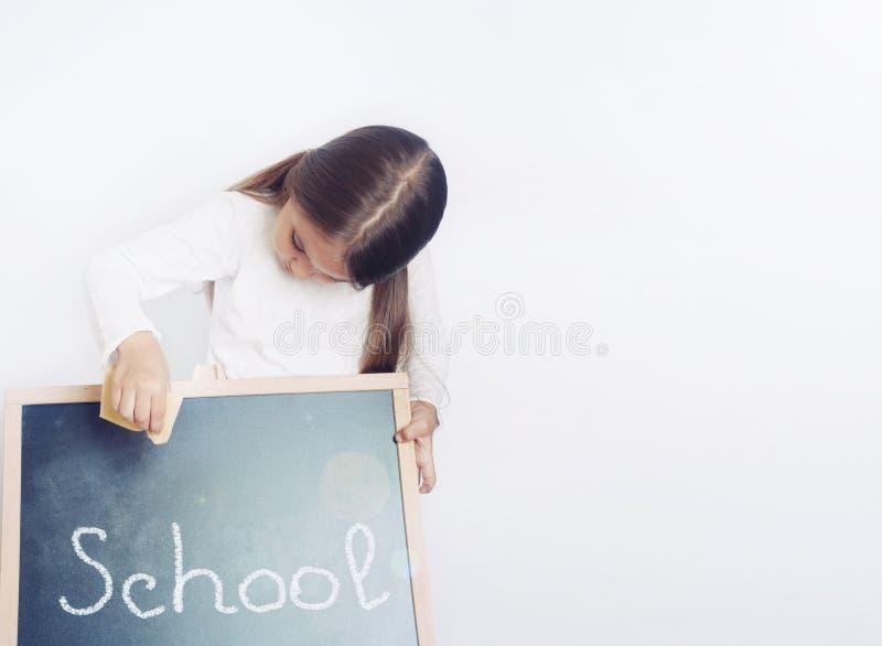 拿着黑板,教育概念的逗人喜爱的可爱的学校女孩 免版税库存照片