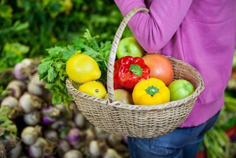 拿着水果和蔬菜在篮子的妇女 免版税库存照片