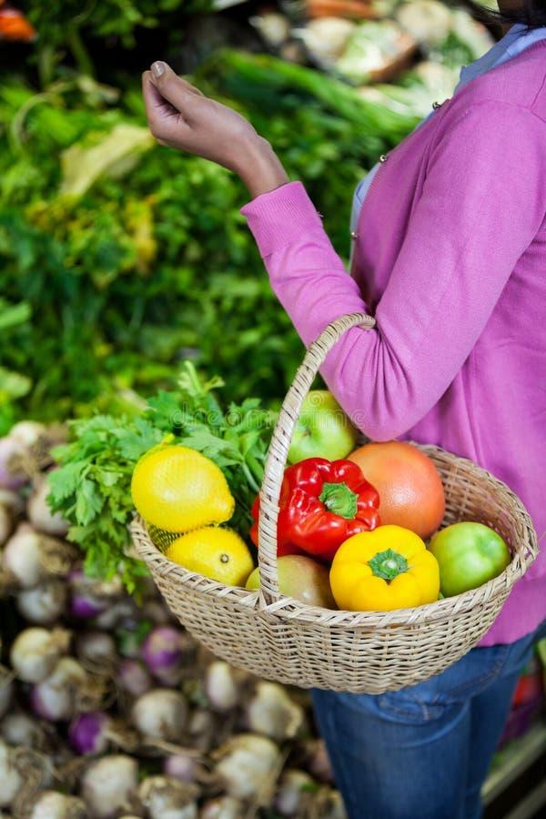 拿着水果和蔬菜在篮子的妇女 库存照片