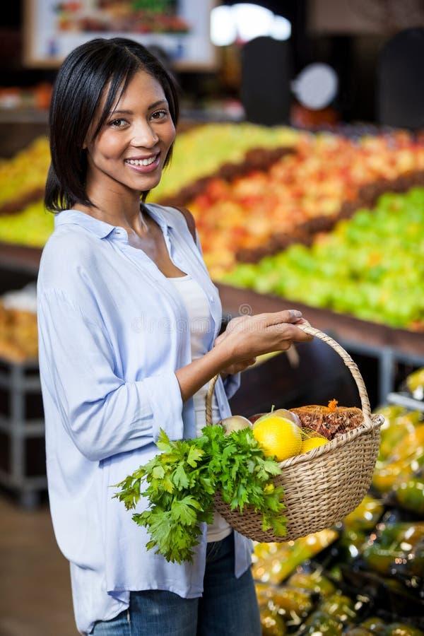 拿着水果和蔬菜在篮子的微笑的妇女 图库摄影