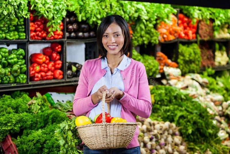 拿着水果和蔬菜在篮子的微笑的妇女 免版税库存图片