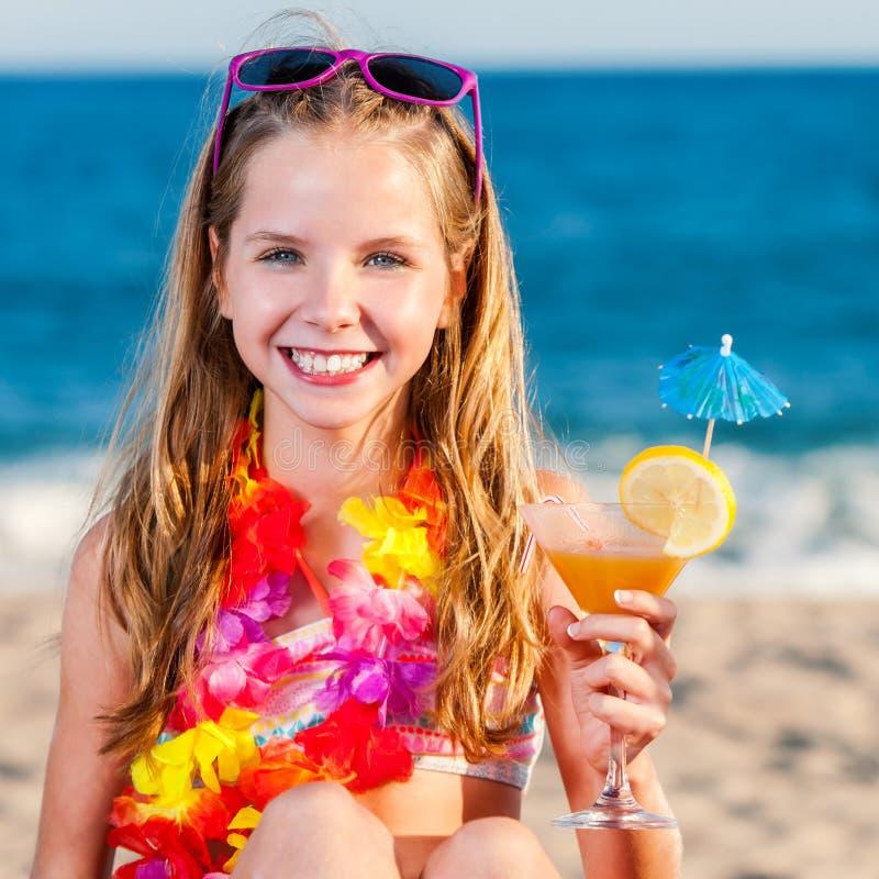 拿着水果鸡尾酒的海滩的逗人喜爱的女孩 免版税库存照片