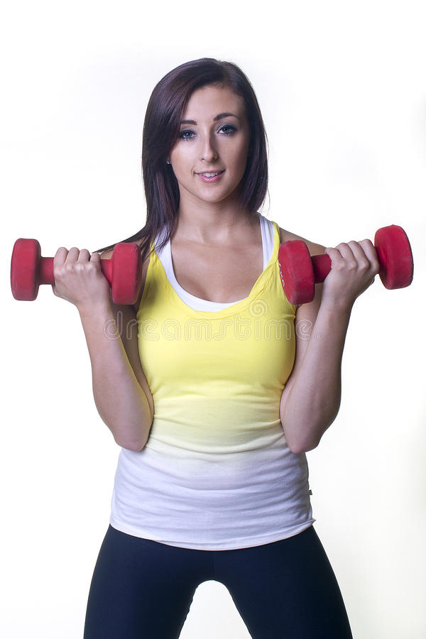 拿着锻炼重量的美丽的少妇 免版税库存图片