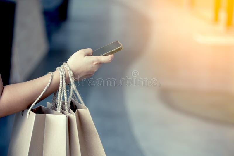 拿着购物袋和使用智能手机的妇女手 免版税库存图片