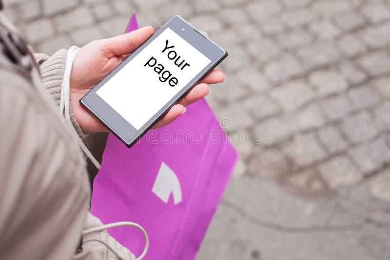 拿着购物袋和手机的妇女。 图库摄影