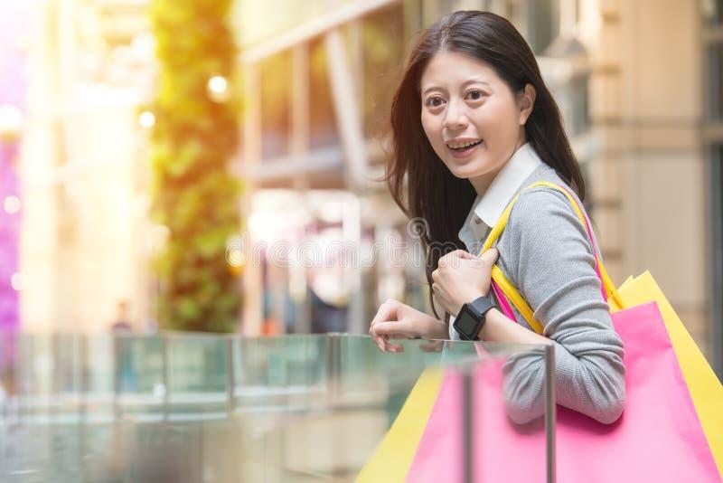 拿着购物袋和穿戴smartwatch的愉快的女孩 免版税库存照片