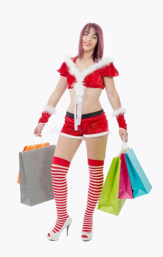 拿着购物袋的美丽的圣诞老人妇女 免版税图库摄影