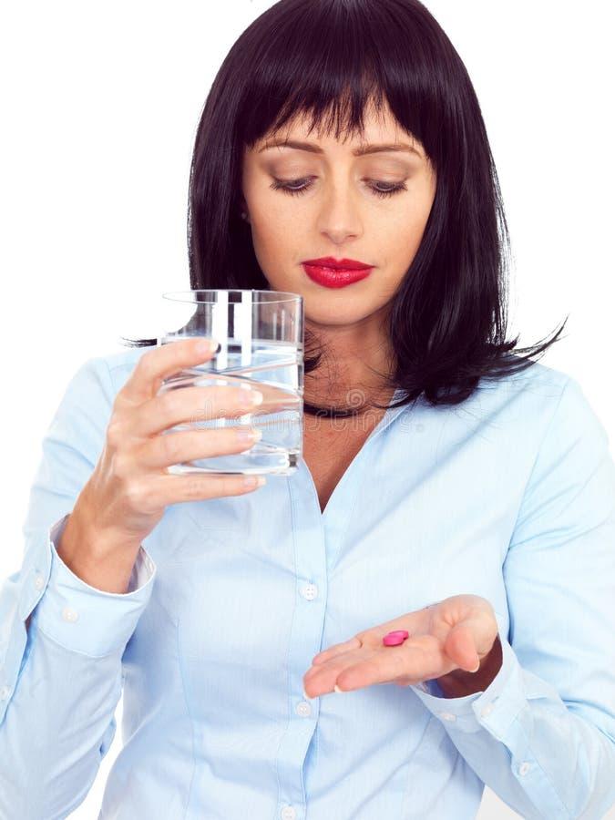 拿着玻璃和采取医学的可爱的深色头发的少妇 免版税库存图片