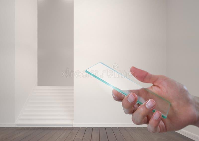 拿着玻璃屏幕的手在现代屋子里 库存照片
