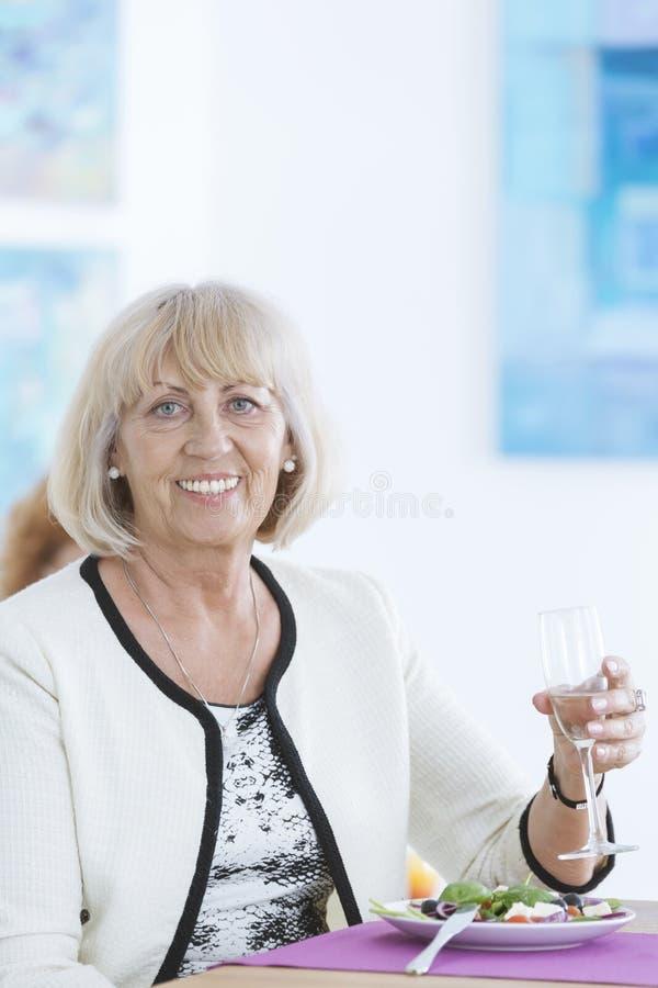 拿着玻璃的夫人 免版税库存图片
