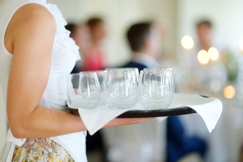 拿着玻璃的盘女服务员 免版税库存图片