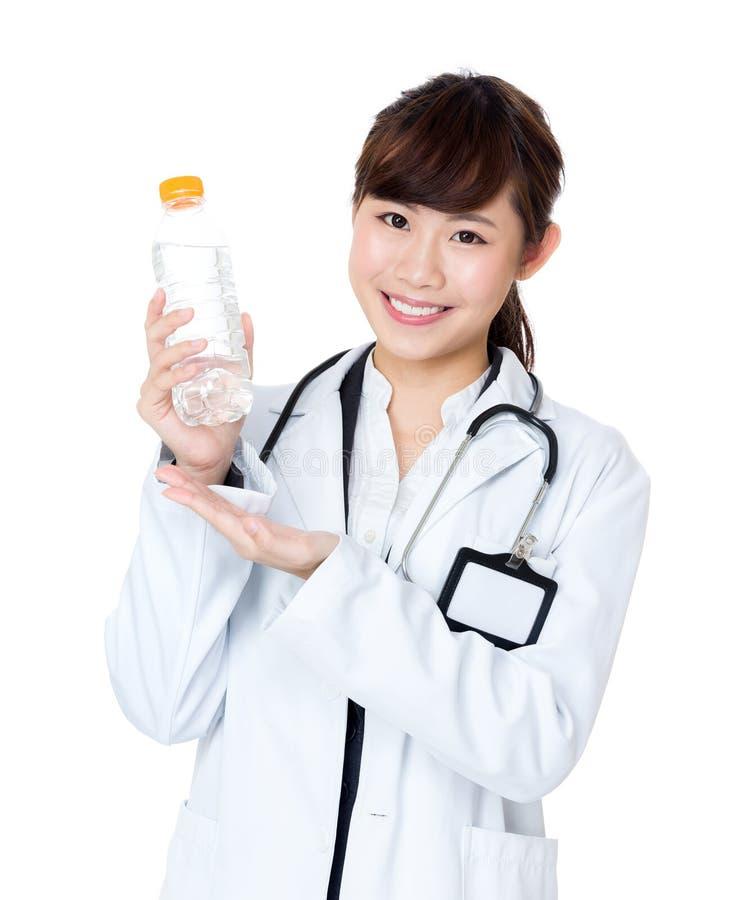 拿着水瓶的亚洲女性医生 免版税图库摄影