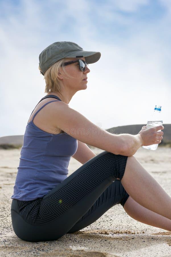 拿着水瓶的疲乏的适合妇女看  图库摄影