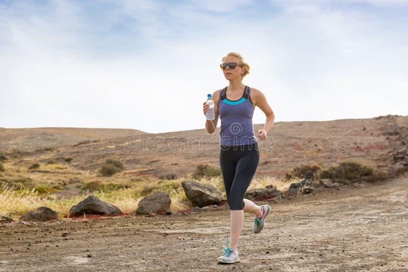 拿着水瓶的活跃妇女运行在土路 免版税库存照片
