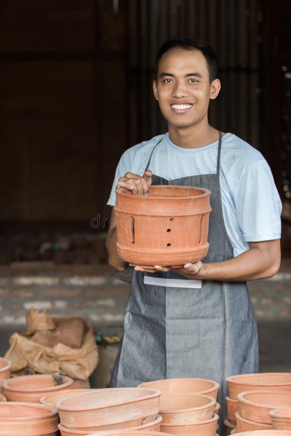 拿着他的产品的微笑的男性陶瓷工在瓦器车间 库存图片