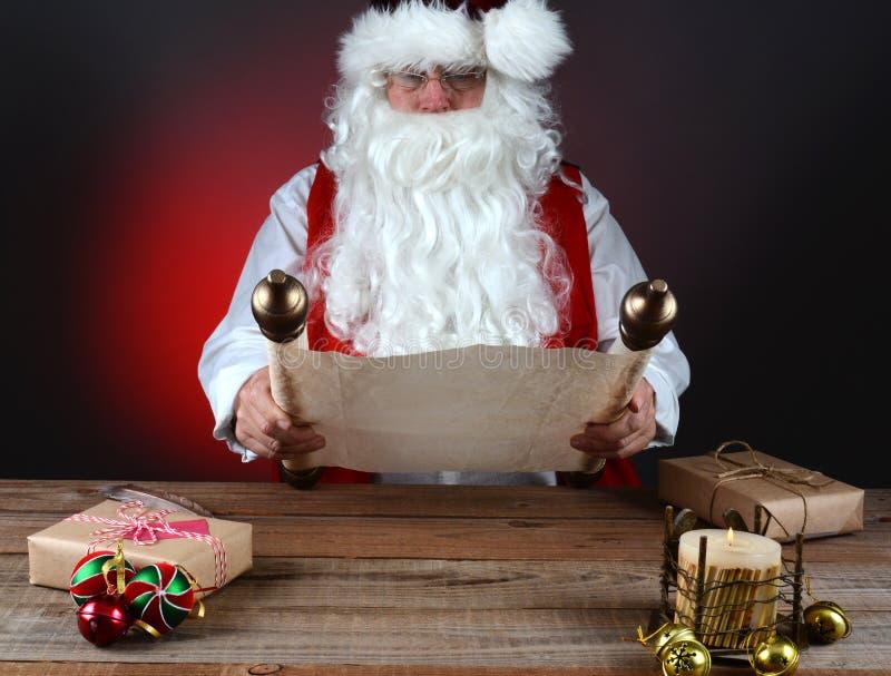 拿着他的名单的圣诞老人 图库摄影