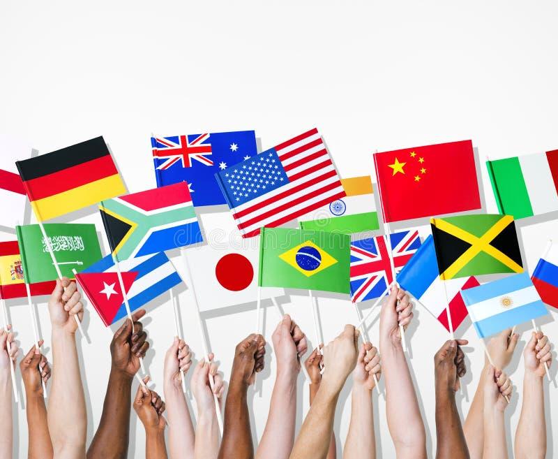 拿着他们的国家的旗子人们 库存图片