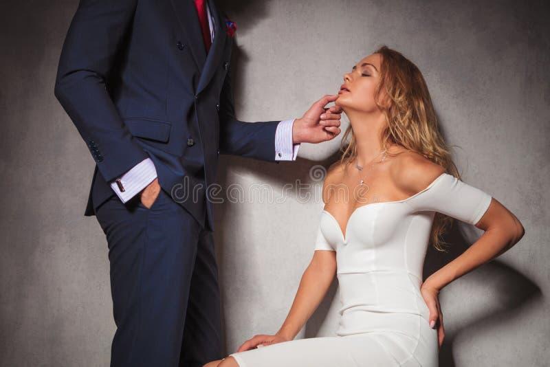 拿着他的妇女的绅士的性感的图片由她的下巴 图库摄影