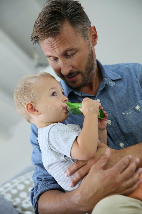 拿着他的小儿子的Fahter吃快餐 免版税库存照片