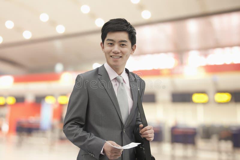 拿着他的票和公文包在机场,北京,中国的年轻微笑的商人 免版税图库摄影