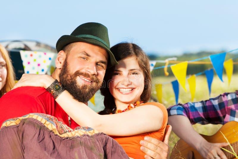 拿着他的胳膊的帽子的微笑的人女朋友 免版税库存照片