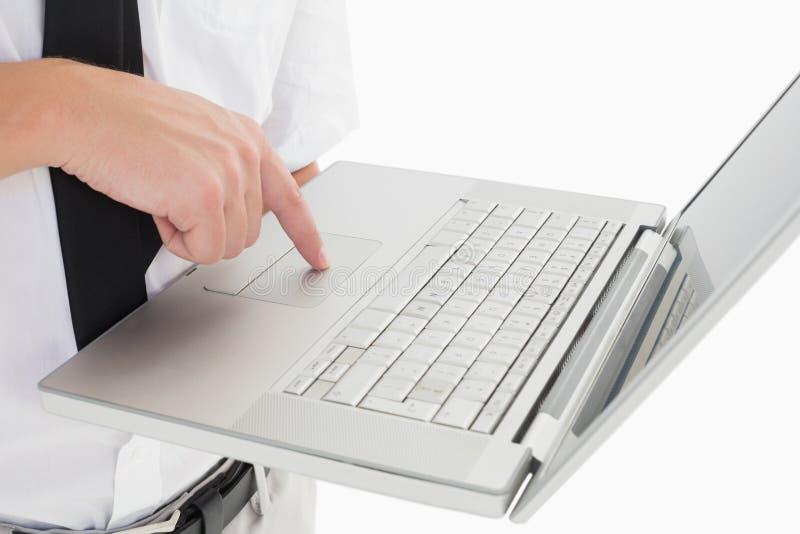 拿着他的膝上型计算机和使用触摸板的商人 免版税库存照片