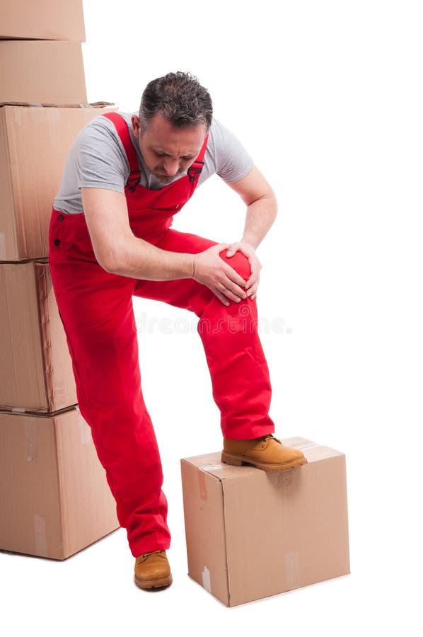 拿着他的膝盖的搬家工人人的充分的身体喜欢伤害 图库摄影